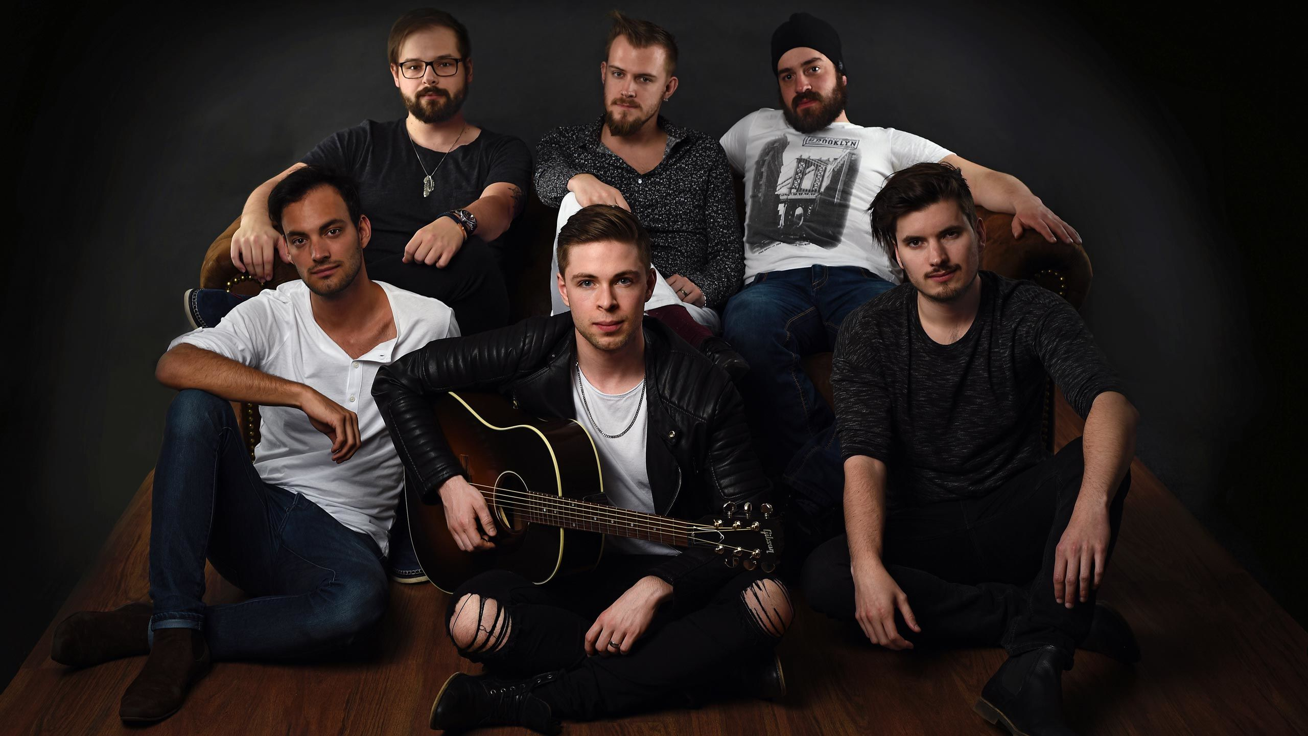 Promotional picture of Reno Gabriel's live band that he plays shows with, in a photo studio, band sitting on a couch, background is dark