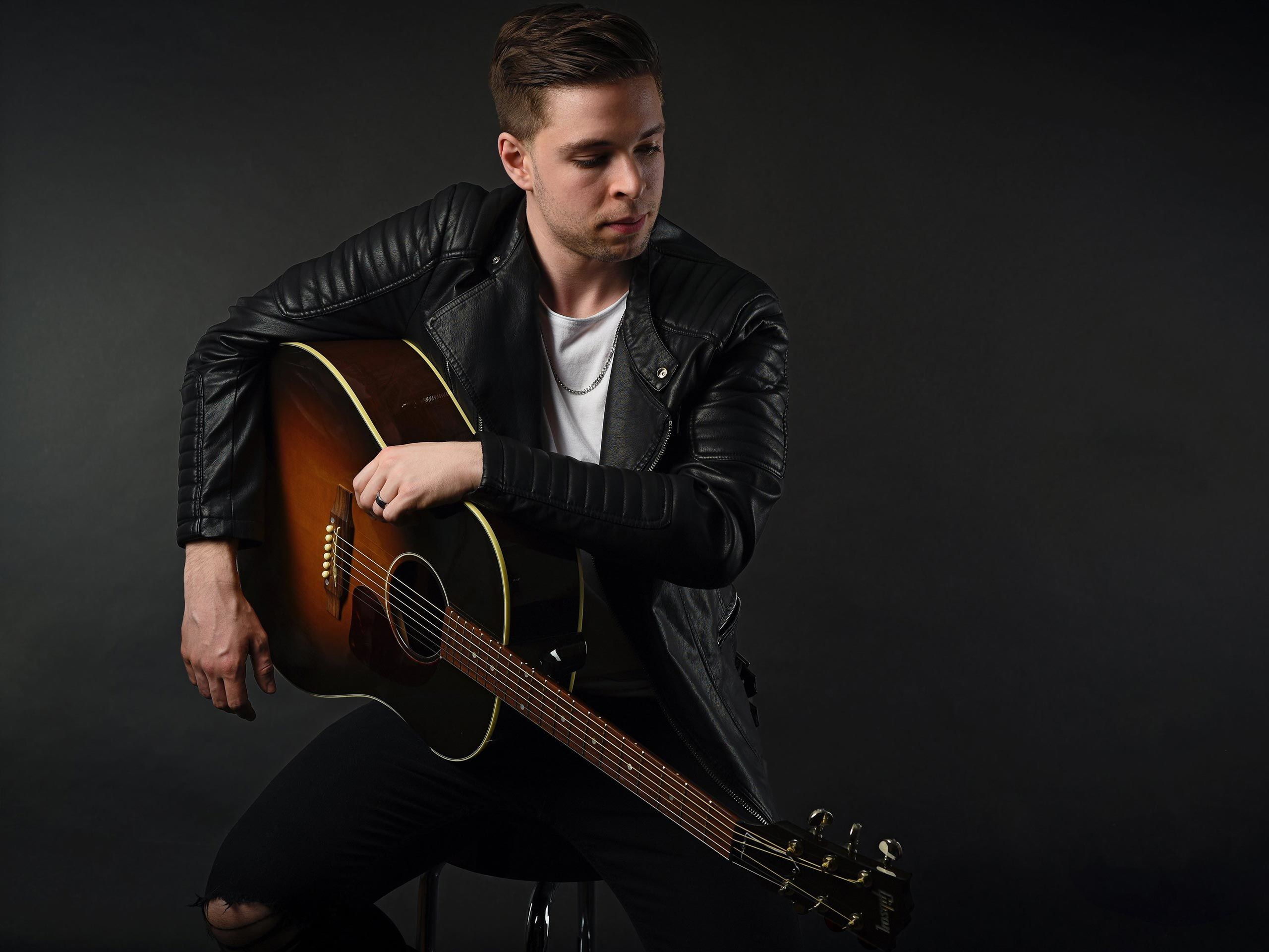 Promotional picture of Reno Gabriel, sitting on a barstool with his Gibson guitar, in a photo studio with a dark background