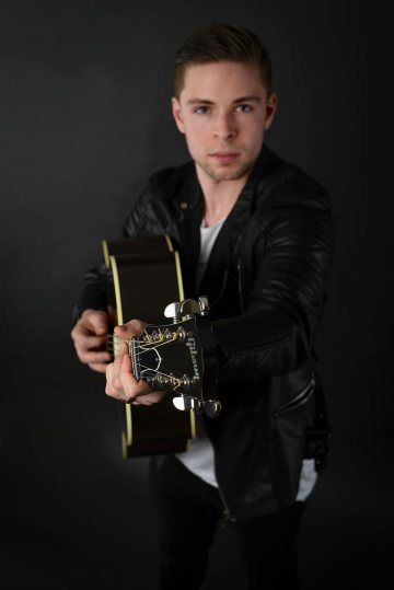 Promotional picture of Reno Gabriel pointing his Gibson guitar right at you in a photo studio with a dark background